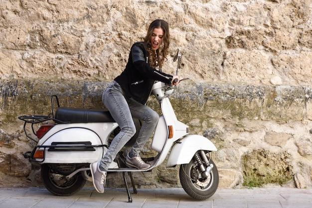 Mujer joven jugando con una moto antigua
