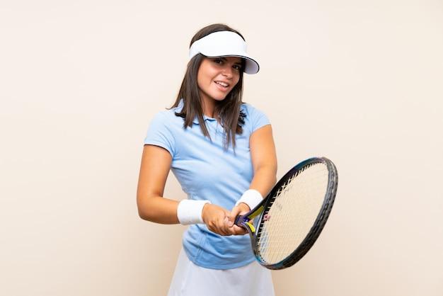 Mujer joven jugando tenis sobre pared aislada