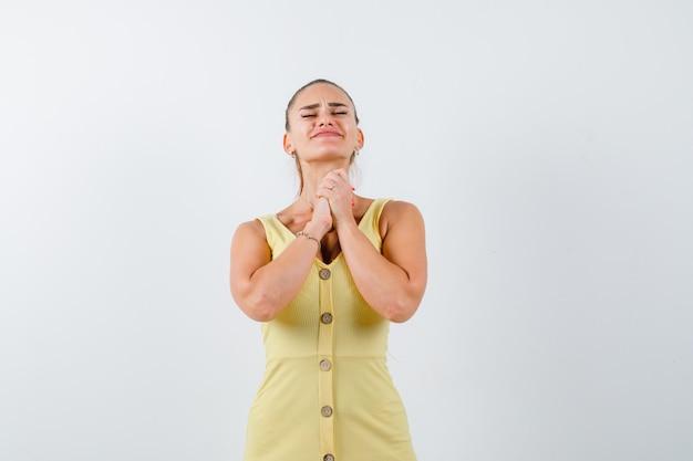 Mujer joven juntando las manos en gesto de oración en vestido amarillo y mirando esperanzado, vista frontal.