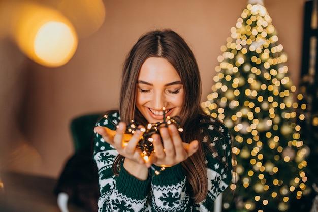 Mujer joven junto al árbol de navidad con luces brillantes de navidad