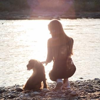 Mujer joven junto al lago con su perro