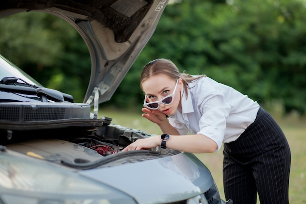 Mujer joven junto a la carretera después de que su automóvil se descompuso. abrió el capó para ver los daños.