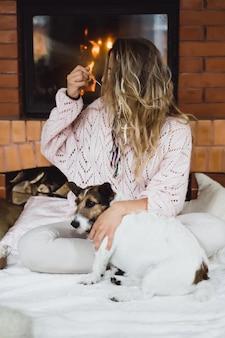 Mujer joven junto a la chimenea cacao bebida con marshmello con perro.