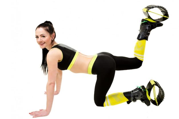 Mujer joven en un kangoo salta zapatos haciendo ejercicios.