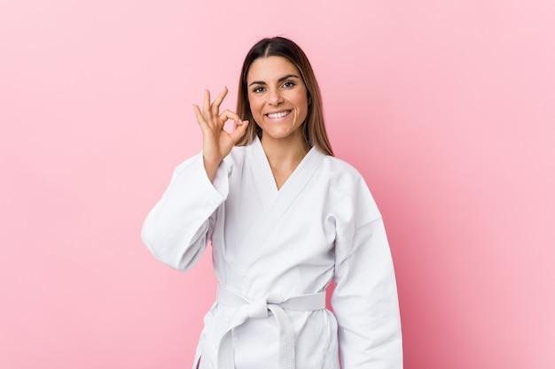 Mujer joven del karate alegre y confiada que muestra gesto aceptable.