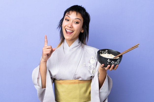 Mujer joven con kimono en azul aislado apuntando hacia una gran idea mientras sostiene un tazón de fideos con palillos