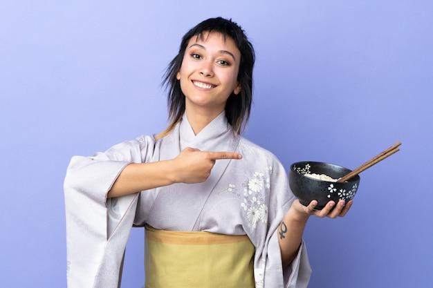 Mujer joven con kimono en azul aislado y apuntando mientras sostiene un tazón de fideos con palillos
