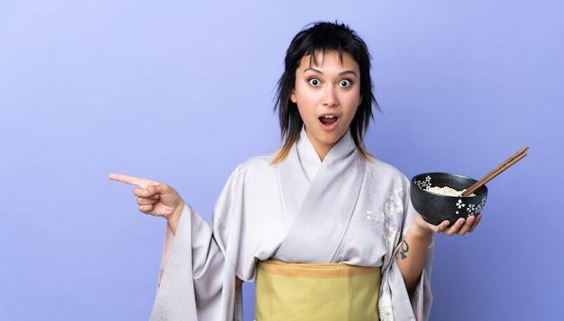 Mujer joven con kimono sobre azul aislado sorprendido y apuntando hacia el lado mientras sostiene un tazón de fideos con palillos
