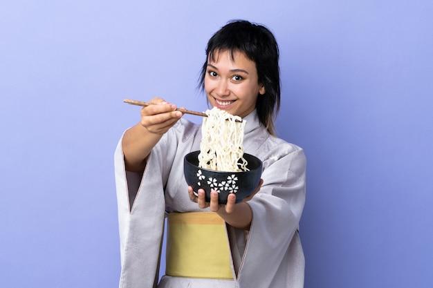 Mujer joven con kimono sobre azul aislado sosteniendo un tazón de fideos con palillos y ofreciéndolo