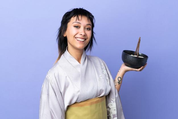 Mujer joven con kimono sobre espacio azul aislado sonriendo mucho mientras sostiene un tazón de fideos con palillos