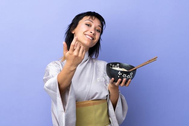 Mujer joven con kimono sobre pared azul invitando a venir con la mano.