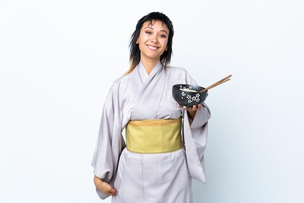 Mujer joven con kimono sosteniendo un plato de fideos sobre blanco aislado sonriendo mucho