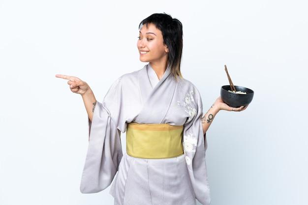 Mujer joven con kimono sosteniendo un tazón de fideos sobre blanco aislado apuntando hacia un lado para presentar un producto