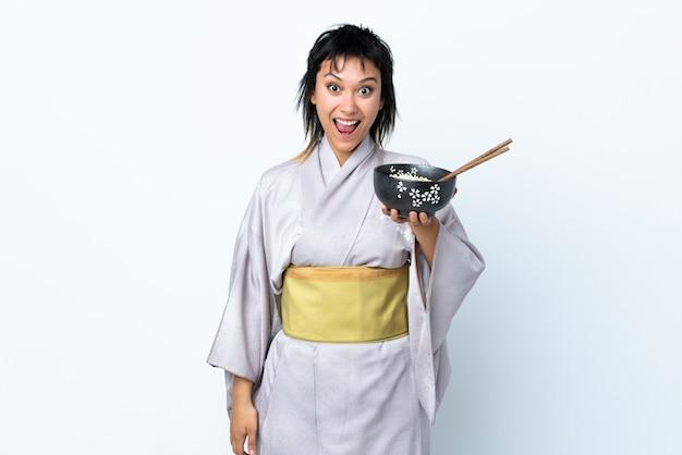 Mujer joven con kimono sosteniendo un tazón de fideos sobre blanco aislado con sorpresa y expresión facial conmocionada