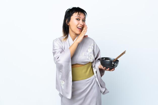 Mujer joven con kimono sosteniendo un tazón de fideos sobre blanco aislado susurrando algo