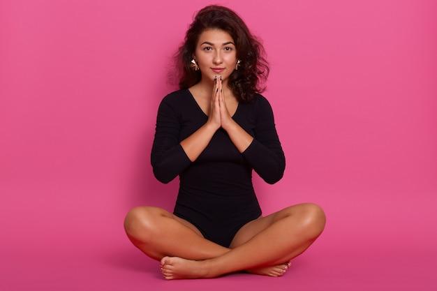 Mujer joven con kombidress, sentada en el piso en postura de loto, adorable niña cogidos de la mano en gesto de oración, morena mujer posando aislada en rosa