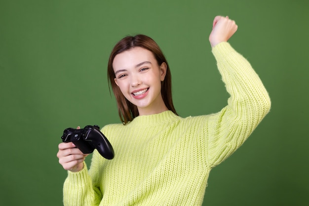 Mujer joven con labios grandes marrones de maquillaje natural perfecto en suéter casual en pared verde con joystick jugando videojuegos gesto ganador