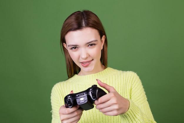 Mujer joven con labios grandes marrones de maquillaje natural perfecto en suéter casual en pared verde con joystick jugando videojuegos