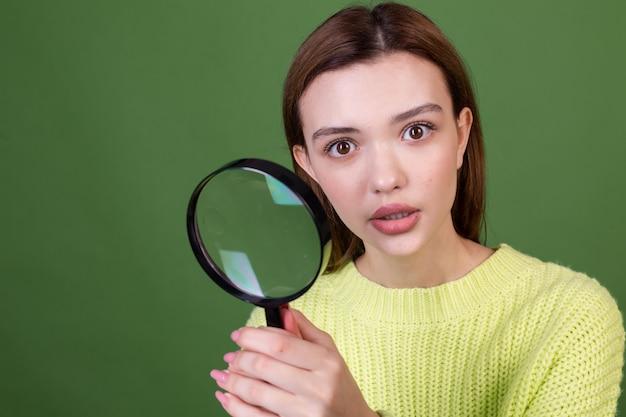 Mujer joven con labios grandes marrones de maquillaje natural perfecto en suéter casual en pared verde con lupa buscando