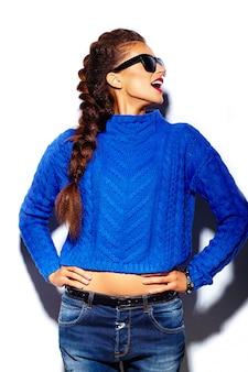Mujer joven con labios rojos y suéter azul en gafas de sol