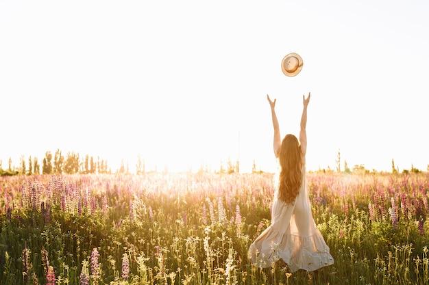 La mujer joven lanza para arriba el sombrero de paja en campo de flor en puesta del sol.