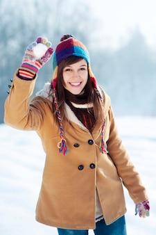 Mujer joven lanzando bolas de nieve