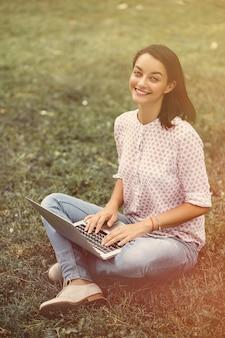 Mujer joven con laptop sentada sobre la hierba verde