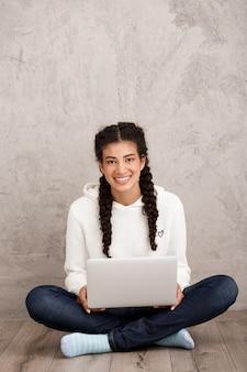 Mujer joven con laptop, sentado en el piso sobre pared beige