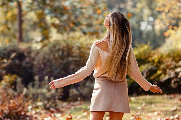 Mujer joven con largo cabello rubio bailando en el parque