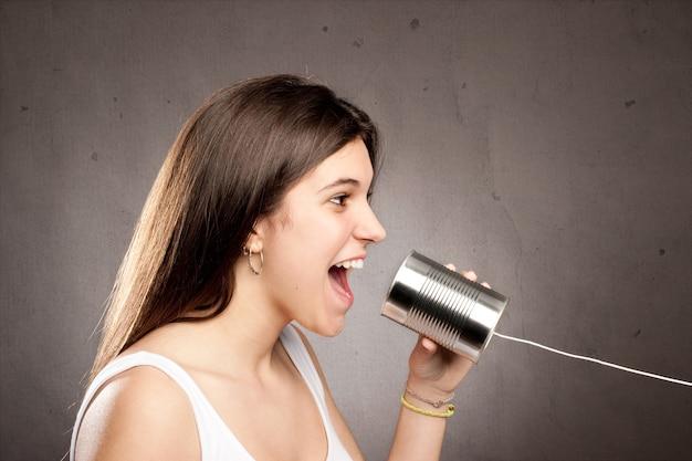 Mujer joven con una lata como teléfono sobre un fondo gris
