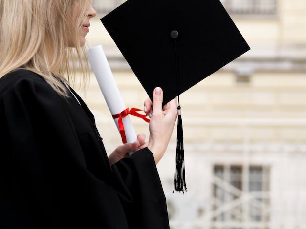 Mujer joven lateralmente celebrando su graduación