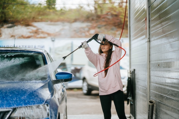 Mujer joven lavando coche azul en el túnel de lavado
