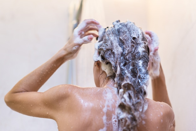 Mujer joven, lavar pelo, en, ducha