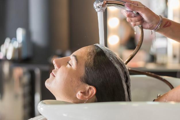 Mujer joven, lavar pelo, en, salón