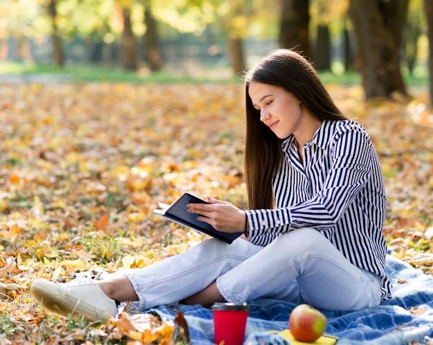 Mujer joven, lectura, aire libre
