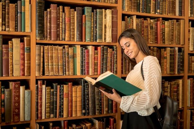 Mujer joven, lectura, cerca, estante