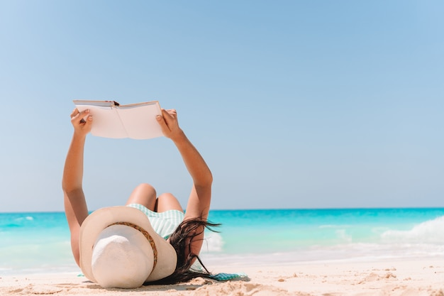 Mujer joven, lectura, libro, en, chaise-lounge, en la playa