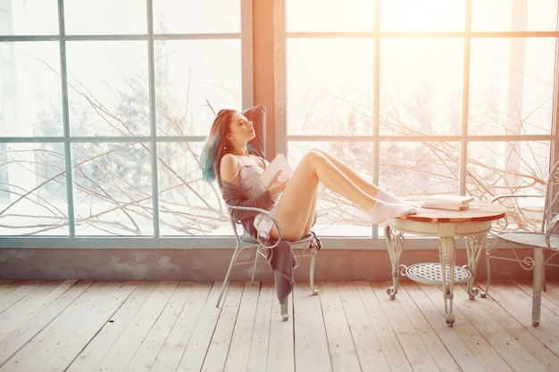 Mujer joven, lectura, libro, sentado, cerca, ventana