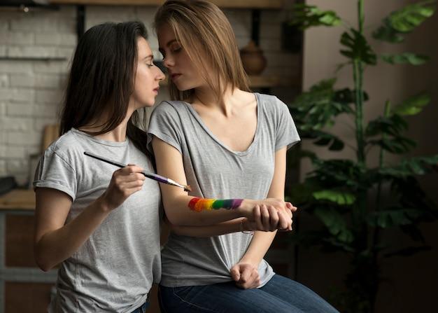 Mujer joven lesbiana pintando la bandera del arco iris sobre la mano de su novia