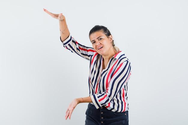 Mujer joven levantando los brazos como mostrando escamas en blusa rayada y luciendo optimista
