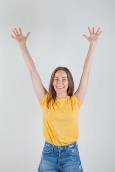 Mujer joven levantando los brazos y las palmas de las manos en camiseta, pantalones cortos y mirando enérgico