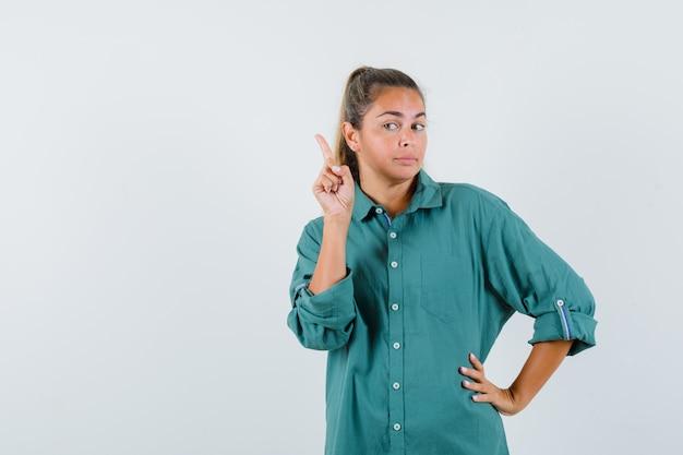 Mujer joven levantando el dedo índice en gesto eureka mientras sostiene otra mano en la cintura en blusa verde y mira pensativa