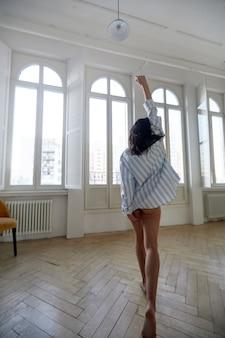 Mujer joven levantando la mano mientras camina hacia la ventana