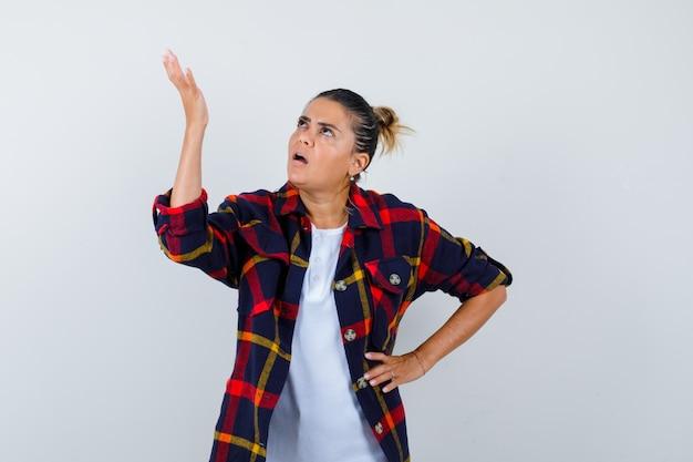 Mujer joven levantando la palma hacia arriba en camisa a cuadros y mirando nostálgico, vista frontal.