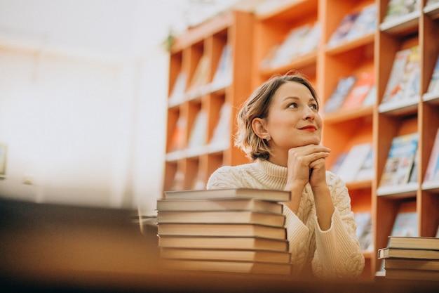 Mujer joven leyendo en la biblioteca