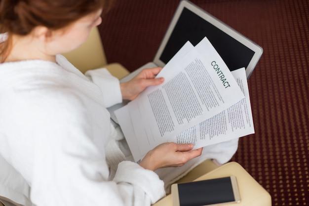 Mujer joven leyendo contratos durante un viaje de negocios