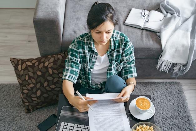 Mujer joven leyendo documentos mientras trabajaba en una computadora portátil en casa
