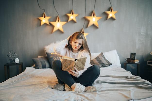 Mujer joven leyendo un libro en la cama, acostada boca abajo sonriendo feliz