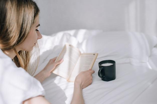 Mujer joven leyendo un libro en la cama, junto a una taza de café. tiempo para un libro