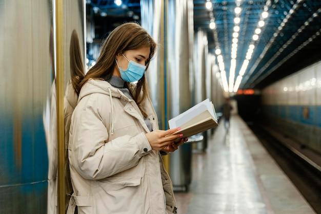 Mujer joven leyendo un libro en una estación de metro